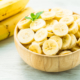 Raw yellow banana fruit slices in wooden bowl