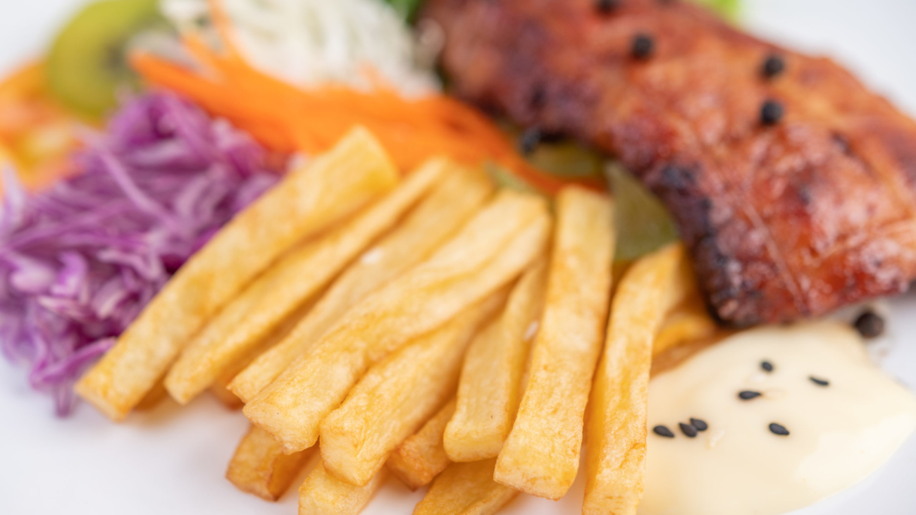Fish steak with french fries, kiwi, lettuce, carrots, tomatoes, and cabbage in a white dish