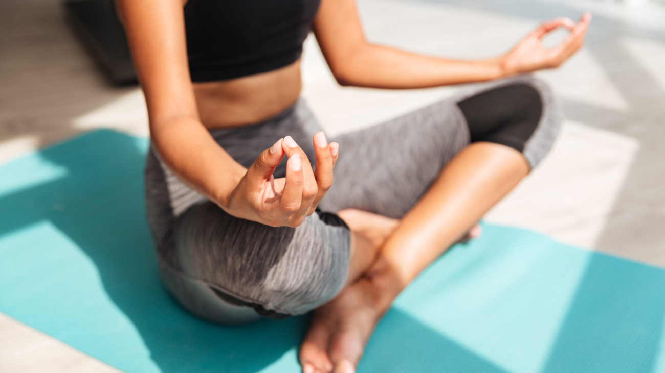 Cropped shot of fitness woman sitting in lotus pose and meditating on floor
